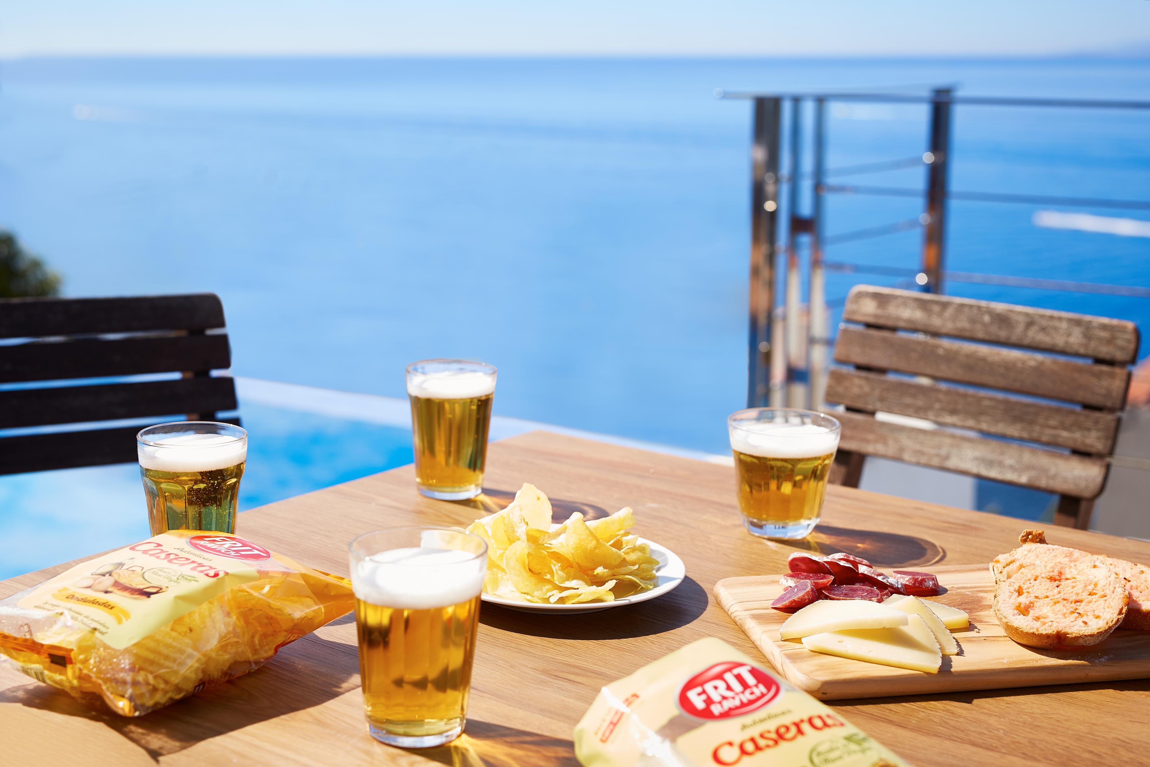 Claves para un aperitivo perfecto. Mesa de bar con cerveza, patatas Caseras Frit Ravich y vistas al mar